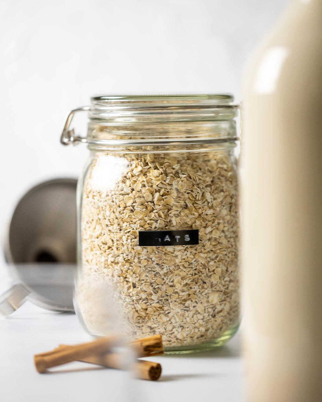 glass jar full of gluten free oats, used to make easy homemade oat milk gluten free