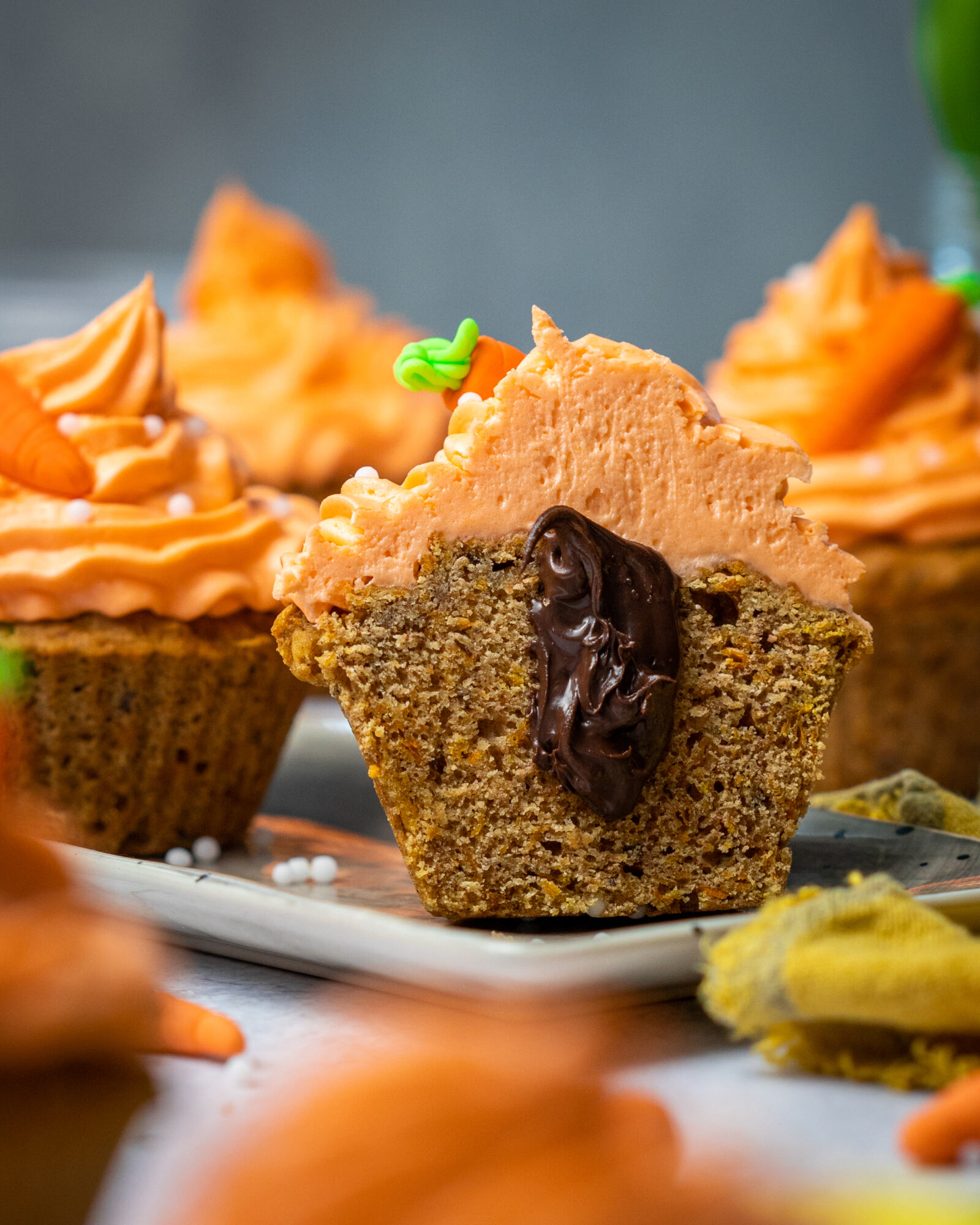 Vegan carrot cake muffins on a white tray, one in focus cut in half with chocolate coming out of it