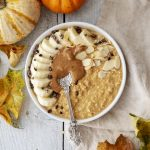 Vegan Pumpkin Spice Porridge photographed from above in a bowl, surrounded by little pumpkins and leaves, banana, nut butter and a spoon placed on top