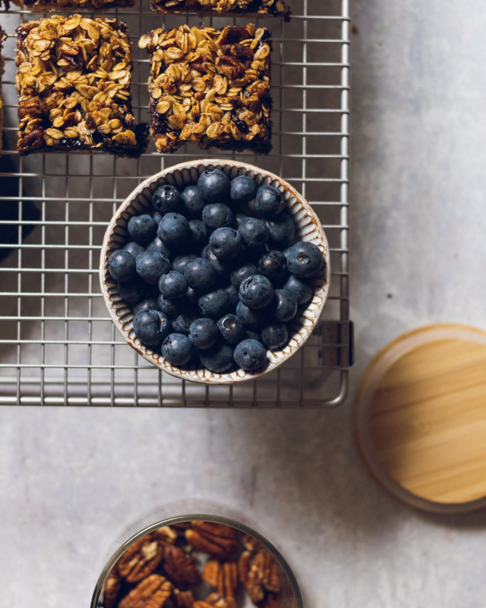 Blueberry Oat Crumble Bars on a cooling rack with a bowl of blueberries