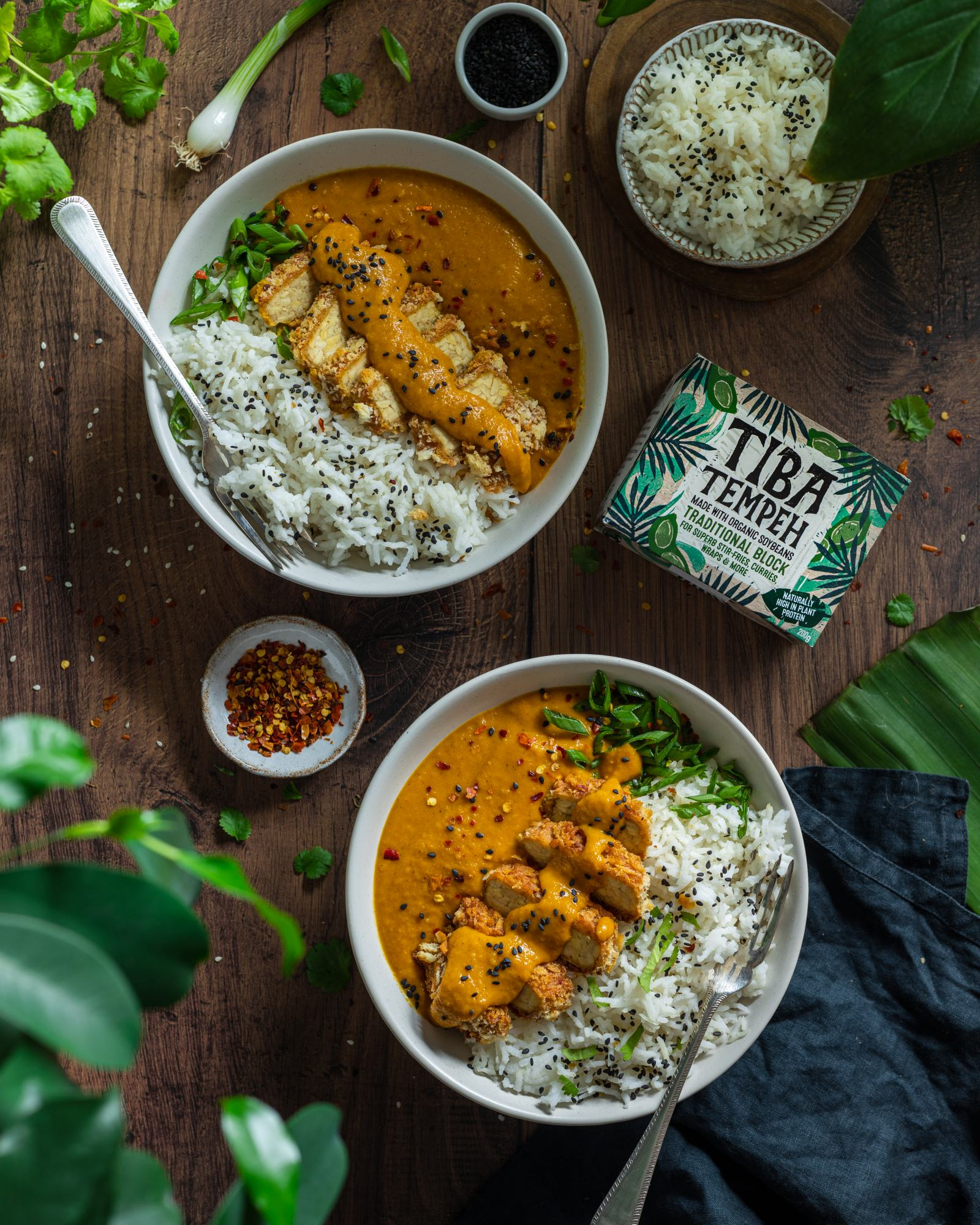 Vegan Katsu Curry with Tempeh - two bowls on a dark backdrop, rice and katsu sauce on each bowl with a fork, sliced crunchy panko coated tempeh on top with a drizzle of sauce, tiba tempeh packaging placed besides the bowls