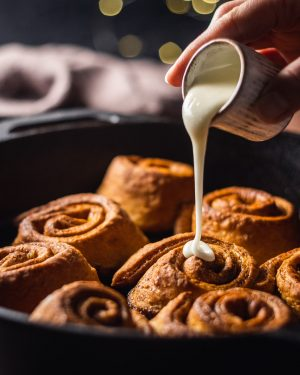 Easy Vegan Cinnamon Rolls photographed from the side with glaze drizzling onto the cinnamon rolls