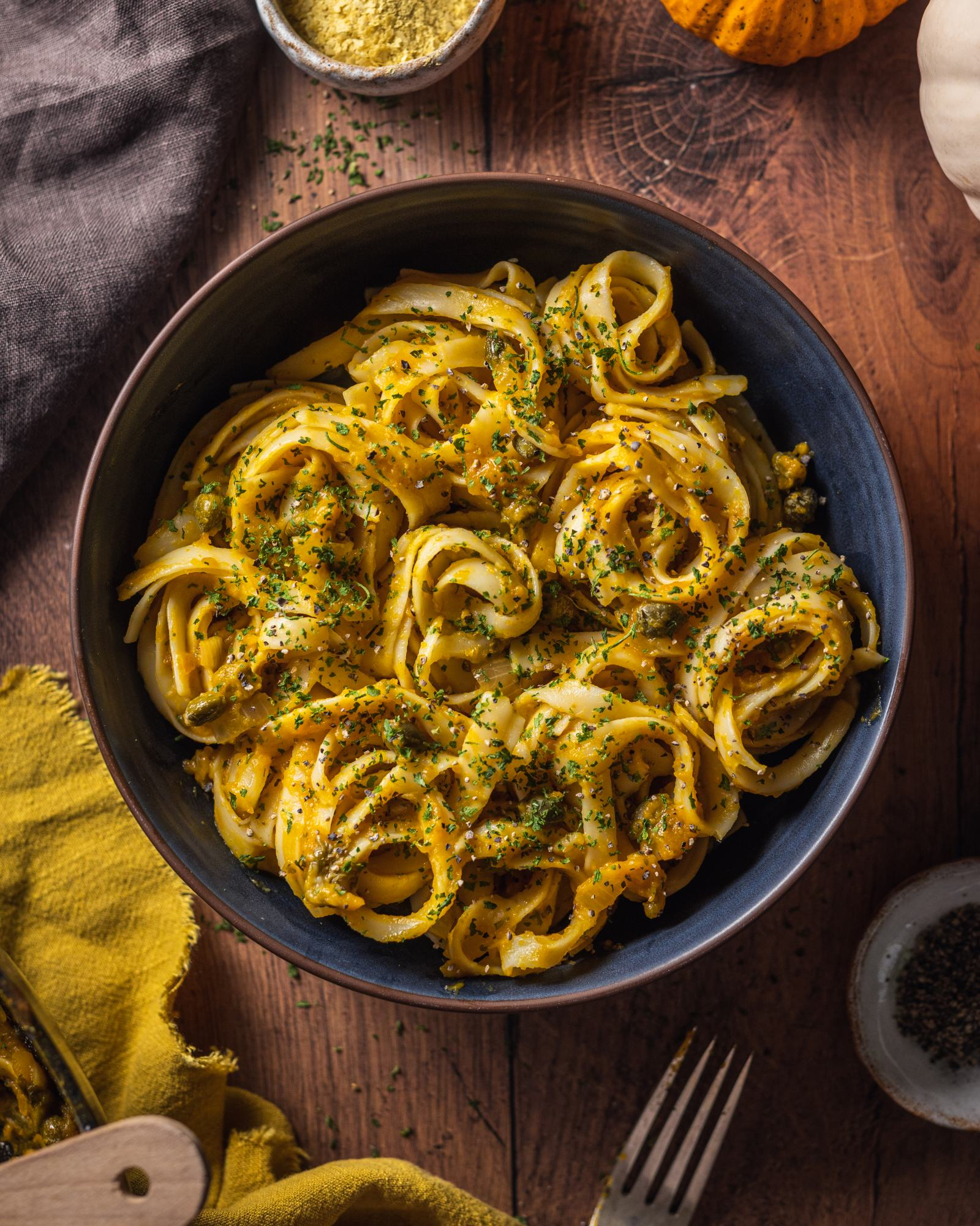 Vegan Pumpkin Linguine Recipe, bowl photographed from above on wooden backdrop, in a black bowl