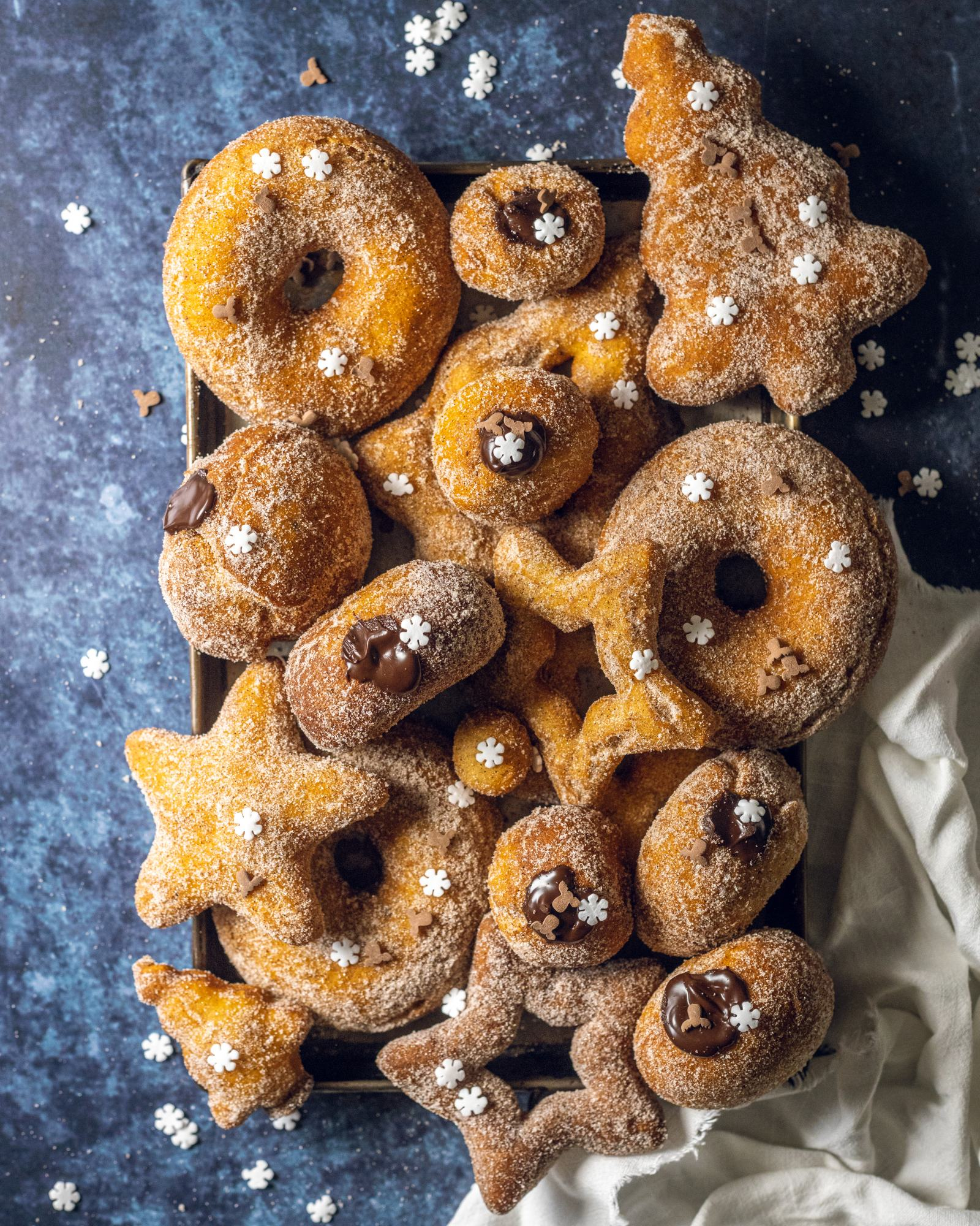 Vegan Donuts with Cinnamon Sugar photographed from above on a dark blue background, different shapes and sizes, some filled with chocolate and sprinkled with snowflake sprinkles
