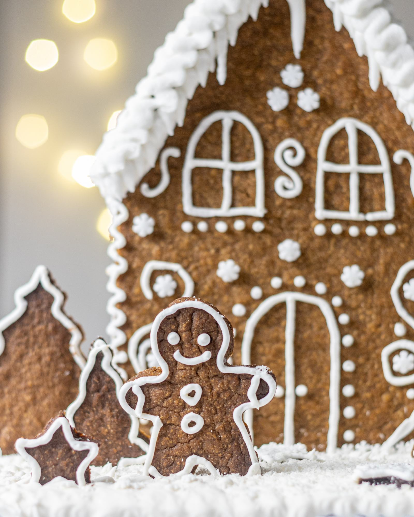 Vegan Gingerbread House, decorated with white buttercream and 'Ho Ho' written on the back, with white roof, photographed on a light backdrop with fairy lights, a gingerbread man standing in front of
