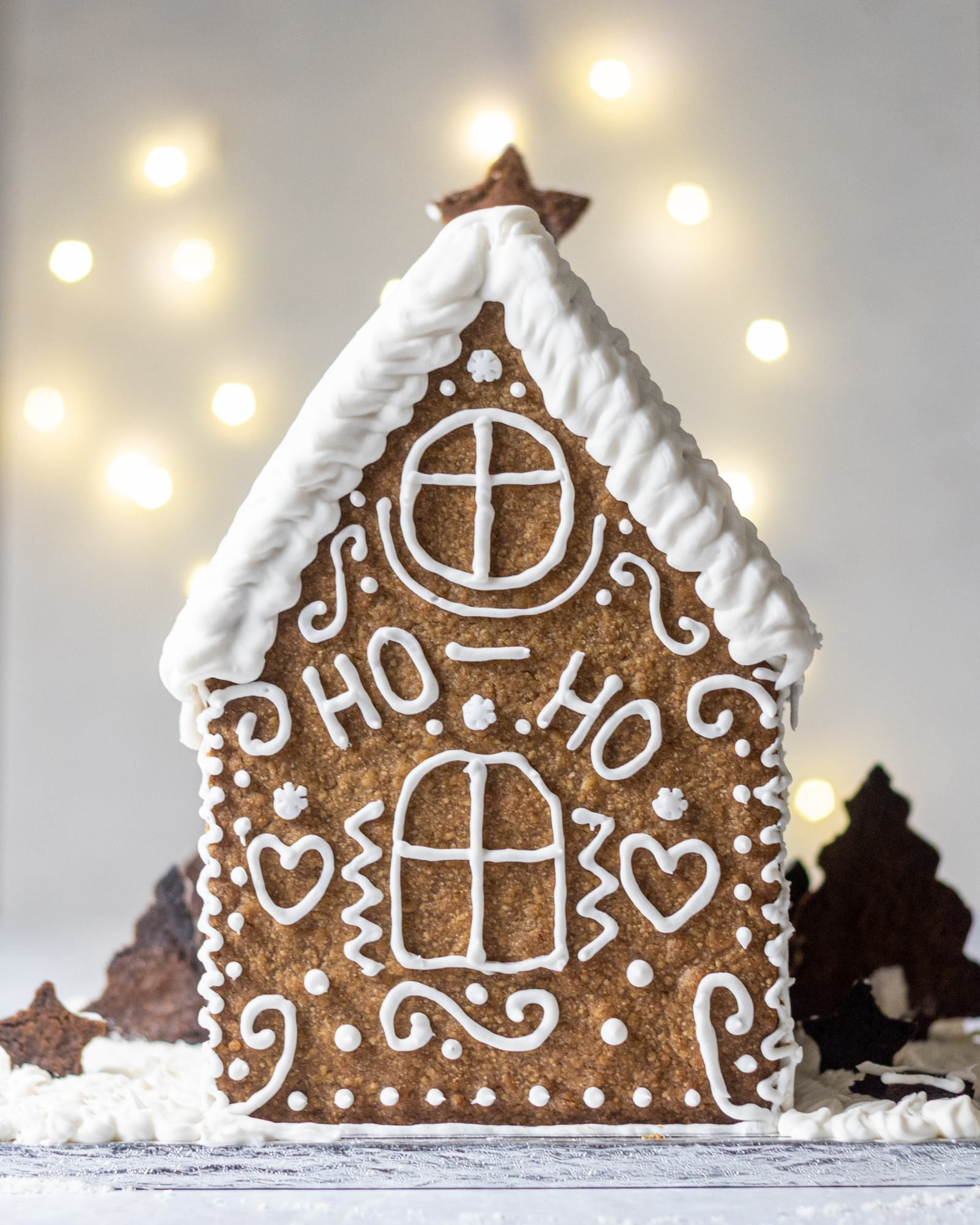 Vegan Gingerbread House, decorated with white buttercream and 'Ho Ho' written on the back, with white roof, photographed on a light backdrop with fairylights
