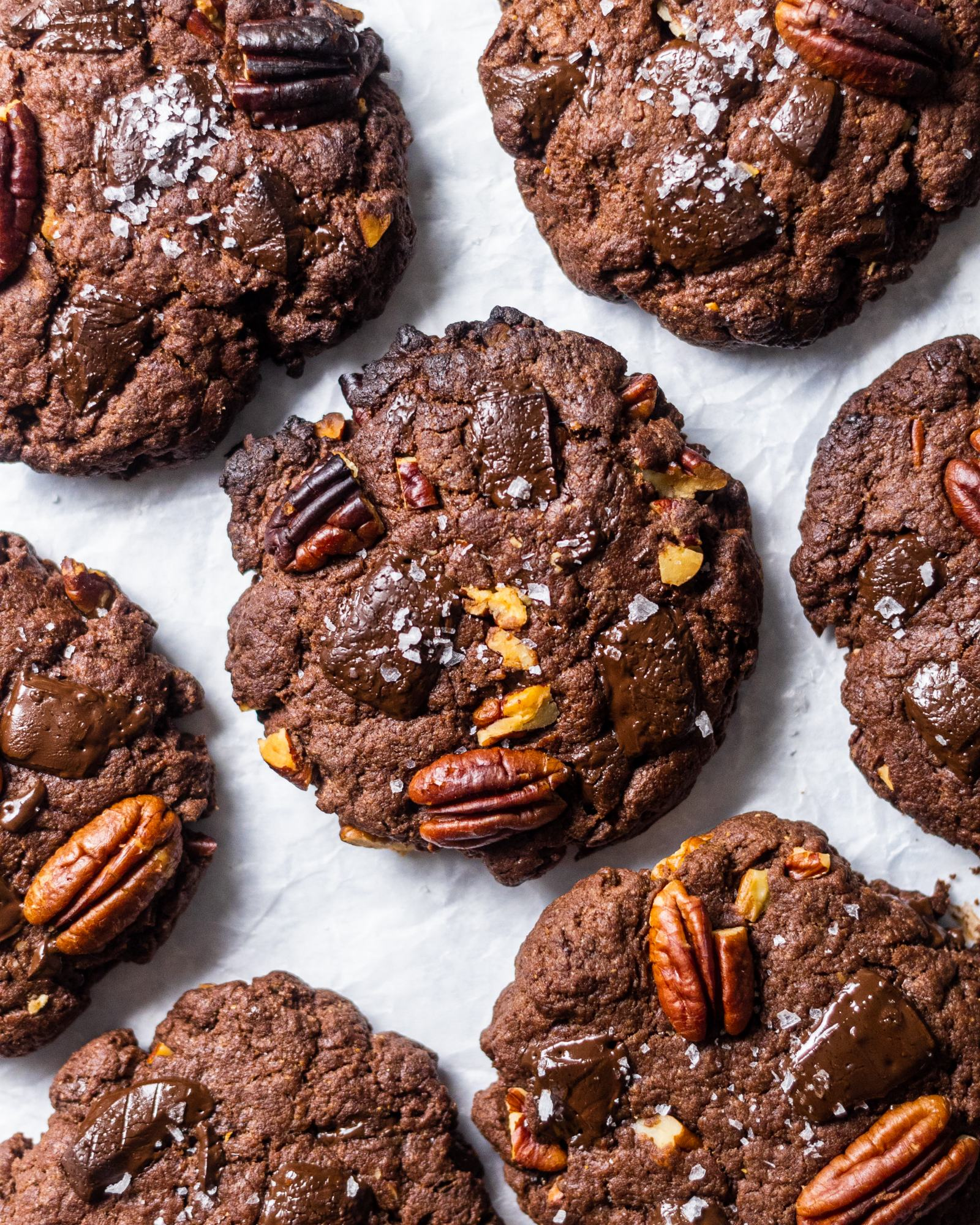 Vegan Triple Chocolate and Pecan Cookies. photographed from above, arranged on white baking parchment