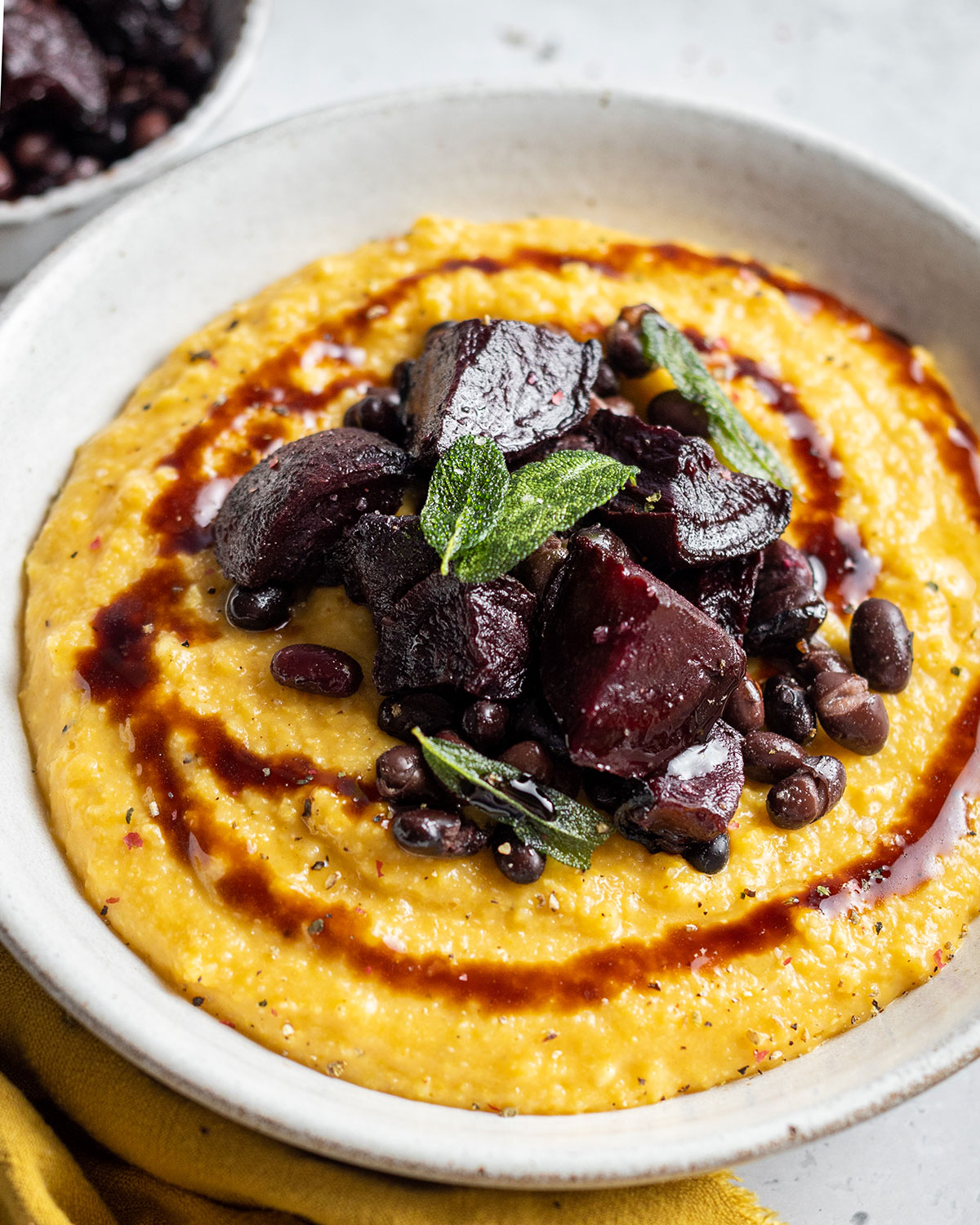 A full bowl of creamy pumpkin polenta topped with roasted beetroot black beans and a balsamic drizzle as well as crispy sage leaves.