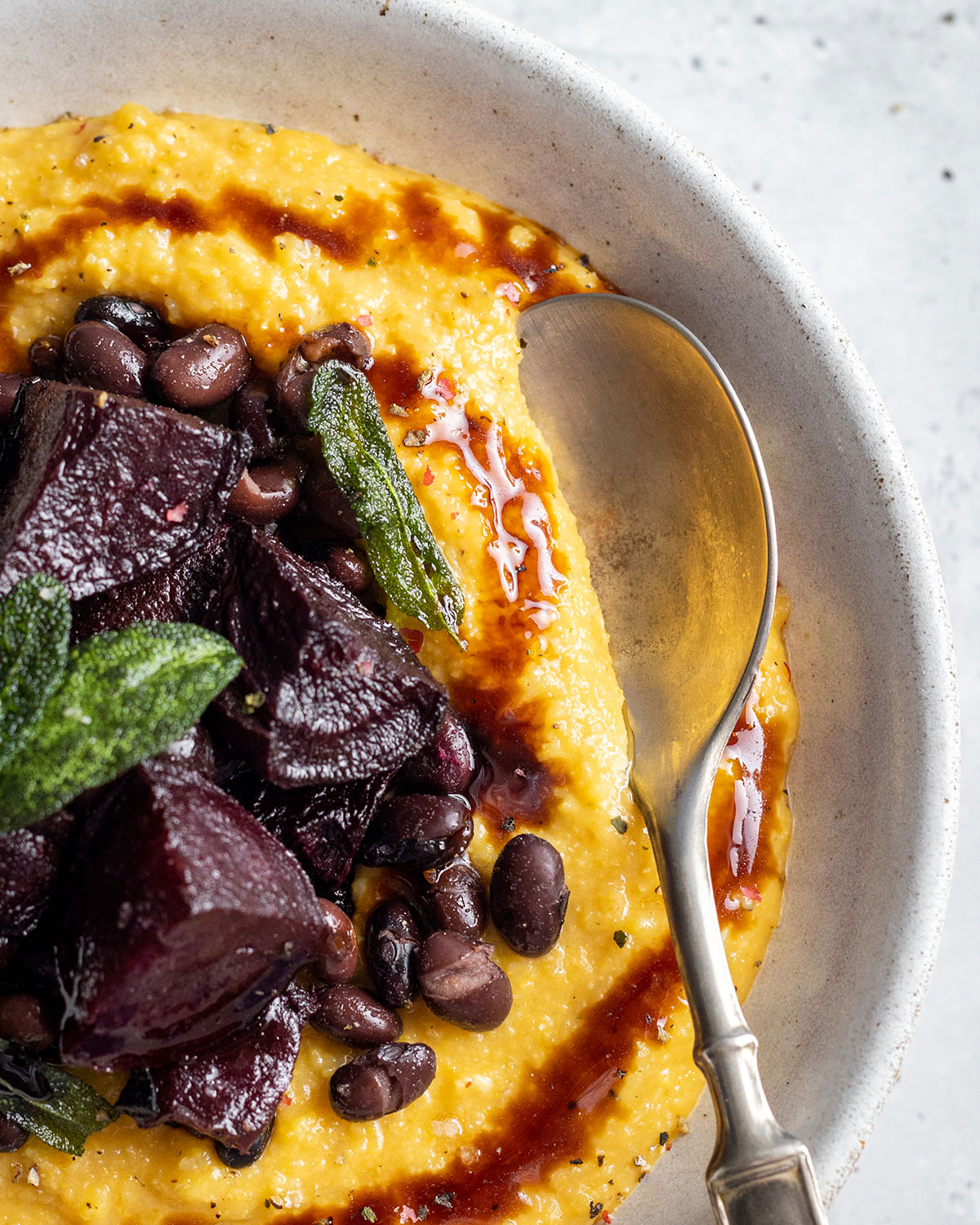 A white bowl filled with creamy pumpkin polenta topped with roasted beetroot and black beans in a balsamic sauce. On top of the bowl there are crunchy fresh sage leaves and a balsamic drizzle.