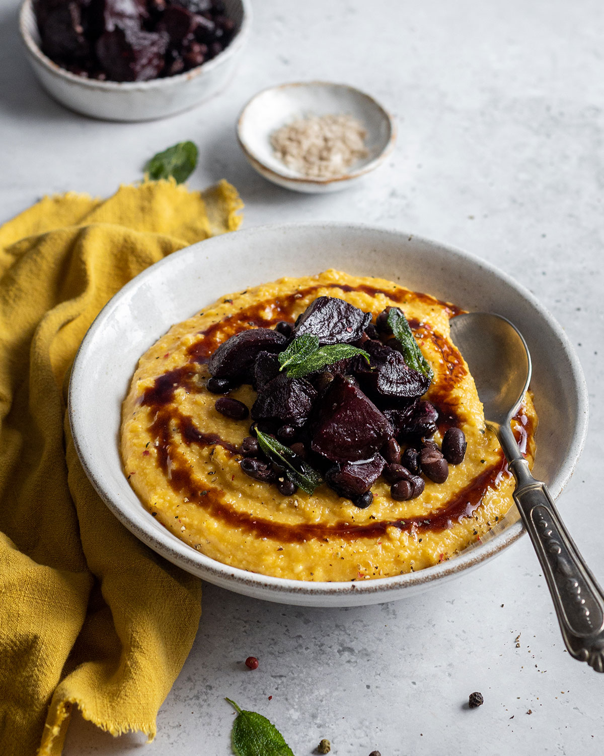 A full shot of a white ball and a white background next to a yellow cloth filled with creamy pumpkin polenta in a yellow colour. The pumpkin polenta is topped with roasted beetroot black beans and a balsamic drizzle.