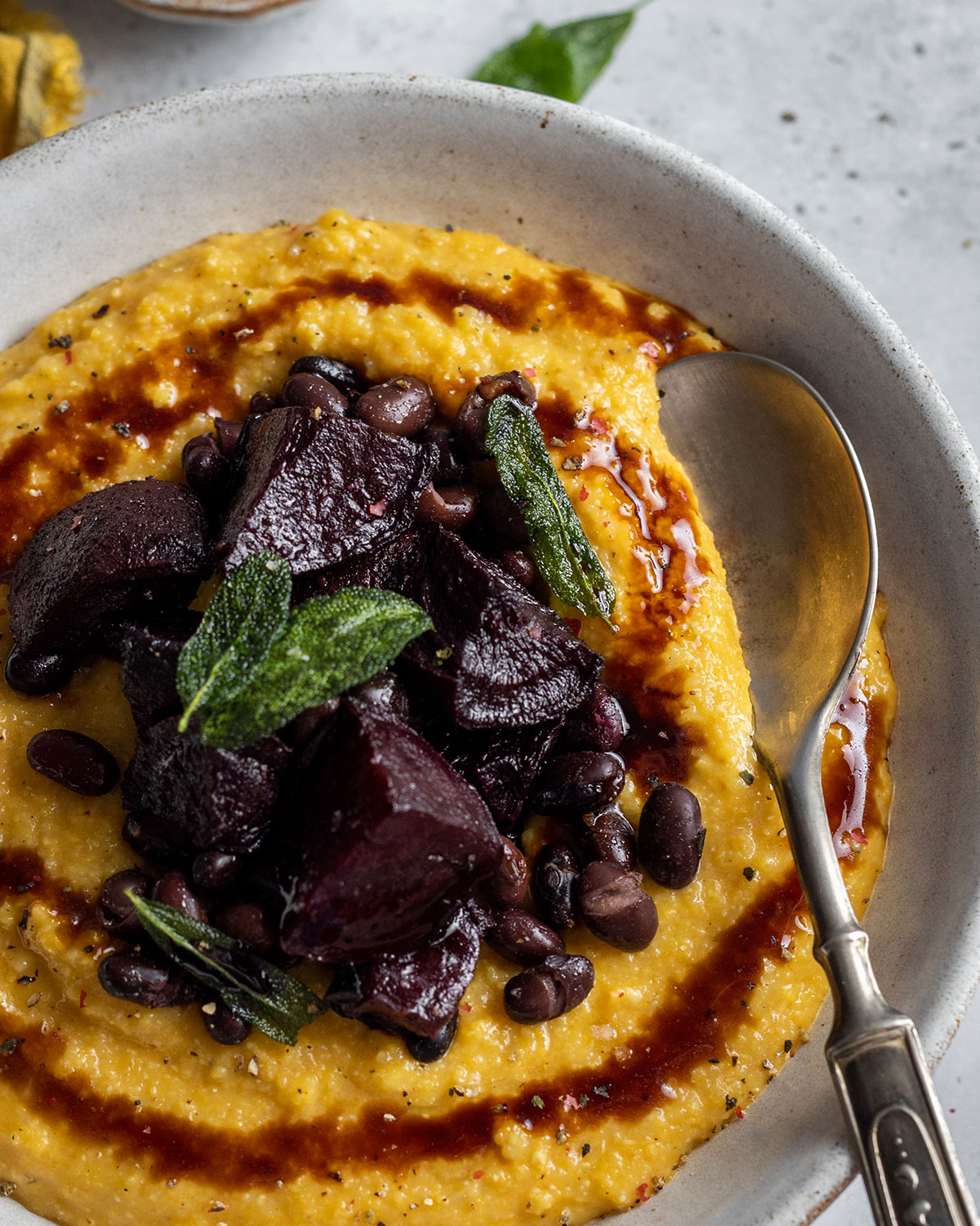 A close-up of a white bowl filled with creamy pumpkin polenta and topped with roasted beetroot in a balsamic sauce together with black beans. There's a spoon in the bowl.
