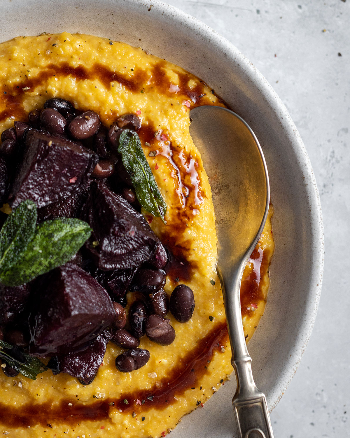 A white bowl with a spoon filled with yellow creamy pumpkin polenta made to a vegan recipe. The pumpkin polenta is topped with roasted beetroot black beans and a balsamic drizzle as well as crispy sage leaves.
